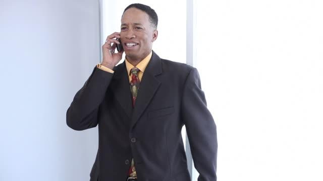 smiling businessman talking on cell phone - bir orta yetişkin erkek sadece stok videoları ve detay görüntü çekimi