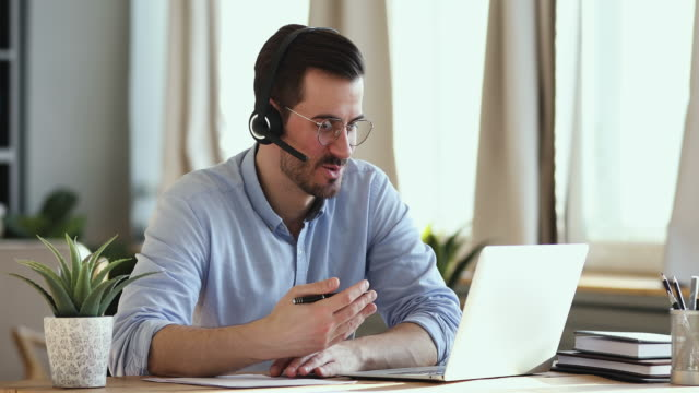 Smiling businessman wear headset making conference video call on laptop Smiling businessman wear wireless headset making conference video call on laptop. Male professional call center agent, hr manager having distance webcam chat job interview on computer in office. zoom call stock videos & royalty-free footage