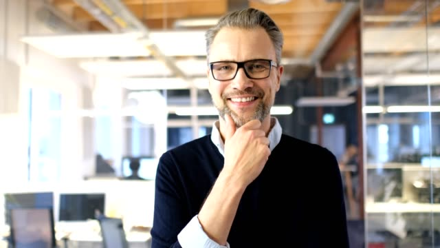 Smiling businessman with hand on chin in office