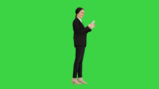 vídeos y material grabado en eventos de stock de empresaria sonriente revisando fotos en su teléfono en una pantalla verde, chroma key - abrigo