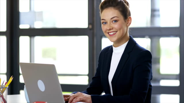Smiling businesswoman typing on laptop at office desk video