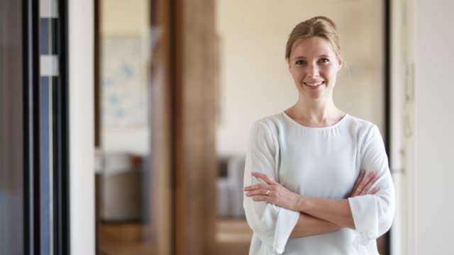 Smiling businesswoman with arms crossed in office Dolly shot of confident businesswoman with arms crossed. Portrait of female professional is wearing smart casuals. She is smiling in office. mid adult stock videos & royalty-free footage