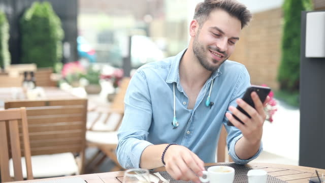smiling casual man sits at restaurant and reads feed on his mobile phone while drinking his coffee - terrazza video stock e b–roll