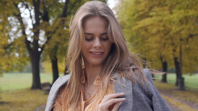 smiling caucasian girl putting on checkered jacket and looking away. nice brunette woman in mustard dress with tweed print standing in the autumn park. - жакет стоковые видео и кадры b-roll