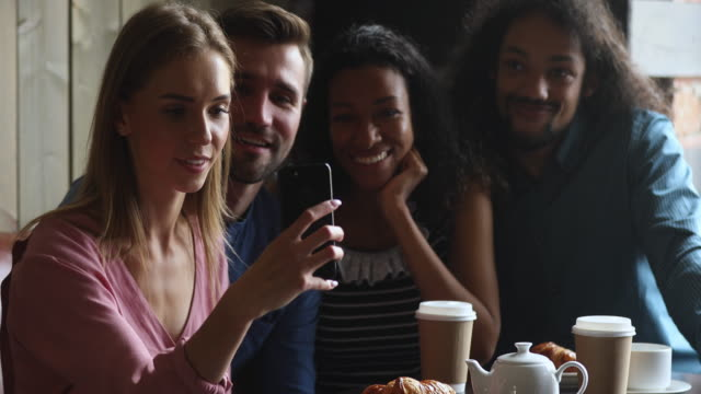 Smiling caucasian woman holding mobile phone, taking selfie with friends.