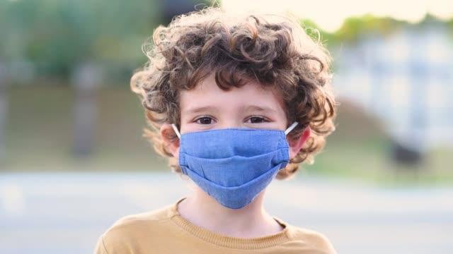 vidéos et rushes de enfant souriant derrière le nouveau coronavirus normal / masque de protection covid-19 - enfant masque