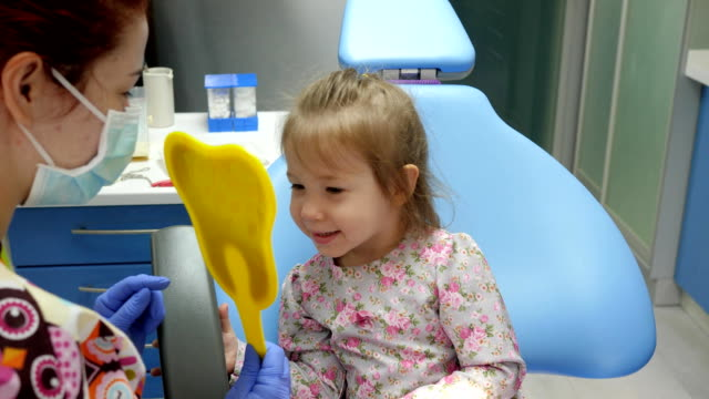 smiling child looking in mirror sitting on dental chair next to doctor in medical mask video