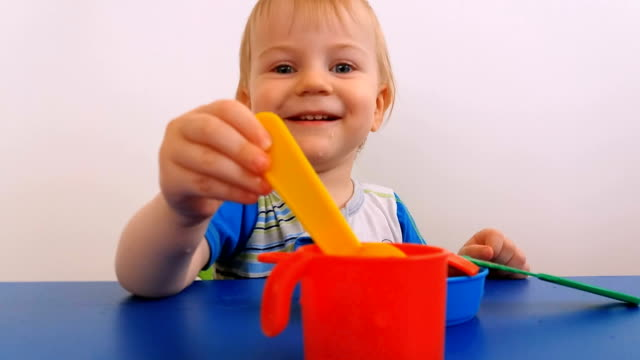 smiling child playing with toy dishes - solo neonati maschi video stock e b–roll