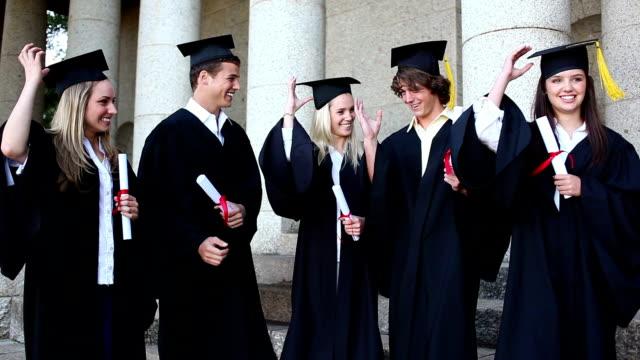 compagni di classe sorridente lanciare i loro berretti - berretto video stock e b–roll