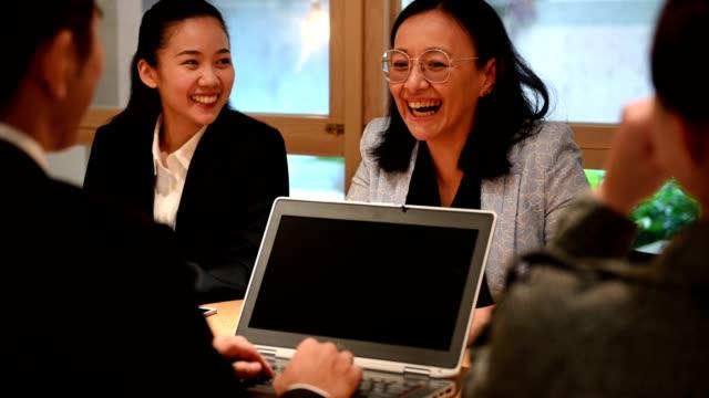 vídeos de stock e filmes b-roll de smiling colleagues during meeting in board room - senior business woman tablet
