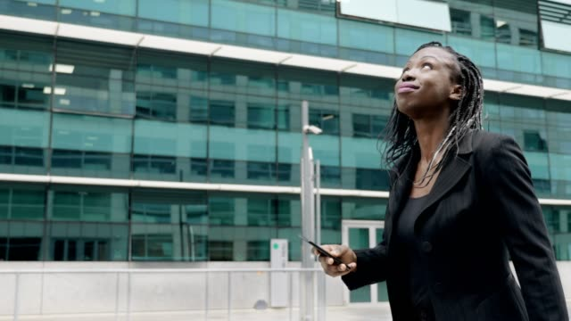 smiling confident african business woman walking typing on her smartphone video