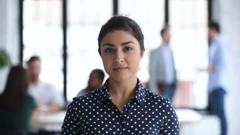 vídeos y material grabado en eventos de stock de sonriendo confiado joven mujer de negocios india mirando la cámara en la oficina - liderazgo