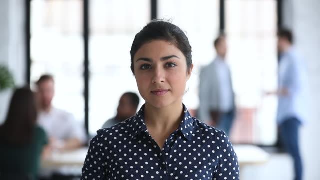 vídeos de stock e filmes b-roll de smiling confident young indian businesswoman looking at camera in office - liderança