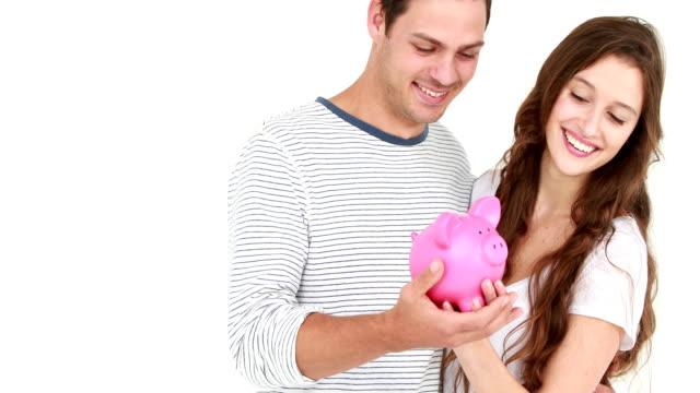 vidéos et rushes de souriant couple holding tirelire cochon - tirelire