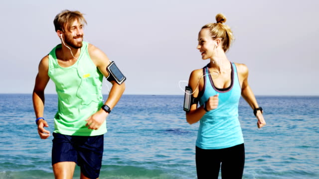 Smiling couple jogging on the beach video