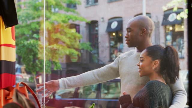 lächelnde paar auf der suche in einem schaufenster kleidung, nahaufnahme - schaufenster stock-videos und b-roll-filmmaterial
