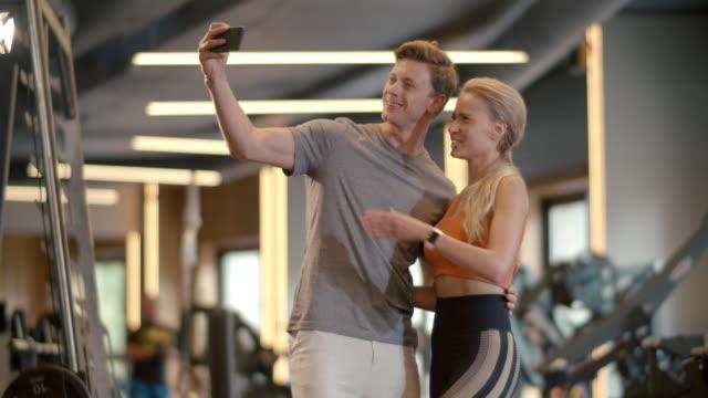 stockvideo's en b-roll-footage met glimlachend paar dat selfiefoto maakt bij gymnastiek. geschikte mens die beeld in sportclub neemt - call center
