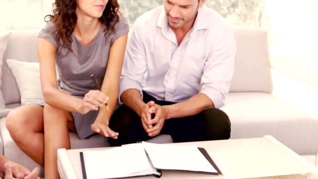 Smiling couple signing contract for new house video
