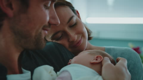 Smiling couple with newborn baby in hospital Close-up of smiling young couple with newborn in hospital. Happy mother and father are admiring sleeping baby. They are in delivery room. family stock videos & royalty-free footage