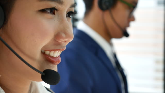 4K Smiling Customer support operators answering a call from customer Dolly shot Customer support operators working telephone operator answering a call Customer service Team concept. Focus at woman. Close up composition. Panning. Tracking on Call center people, 4K(UHD) Apple ProRes 422 (HQ) 3840x2160 format hands free device stock videos & royalty-free footage