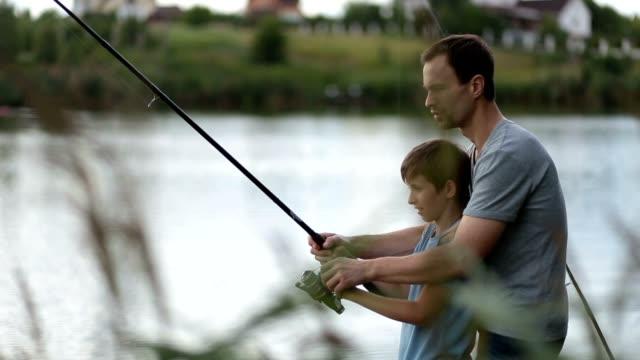 Sonrisa de padre e hijo de pesca y relax en la charca. - vídeo