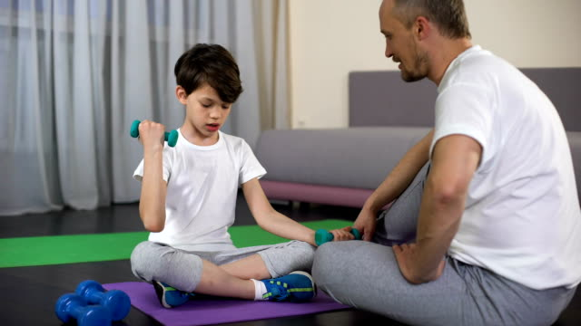 Smiling dad praising son during home workout, teaching him doing fitness, sport video