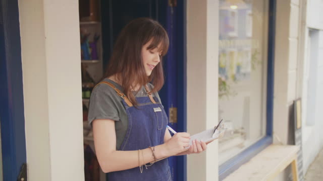 Smiling Deli Owner Writing In Clipboard Outside Shop video