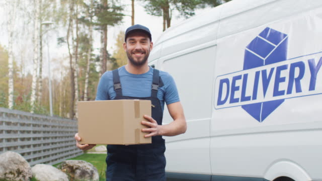 Smiling Delivery Man Comes Out of His Cargo Van with Cardboard Boxes and Goes Towards Camera. video