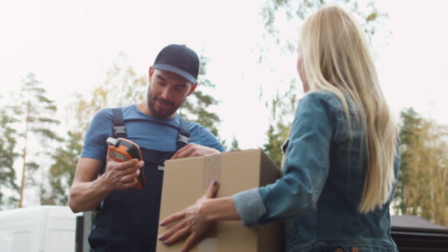 Smiling Delivery Man Hands Over Parcel after Recipient Signs Electronic Signature Device. Weather is Sunny and Warm. video