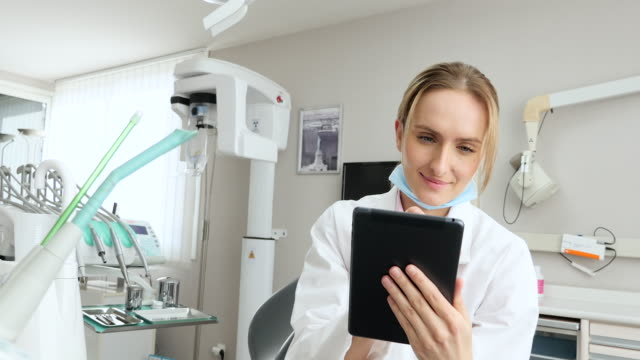 smiling dentist working on tablet - dentist стоковые видео и кадры b-roll