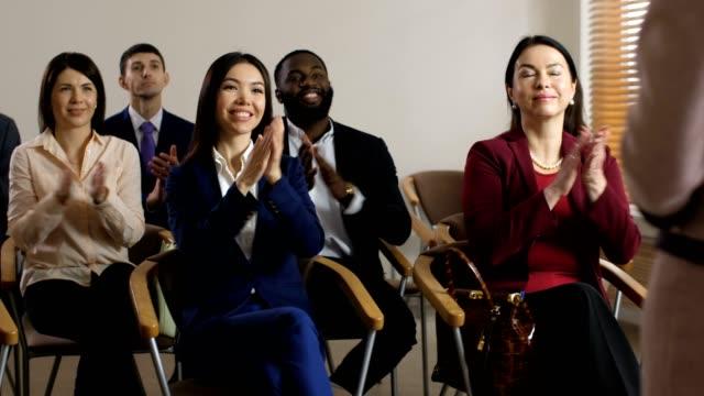 vídeos de stock e filmes b-roll de smiling diverse audience cheering spokesperson - orador público