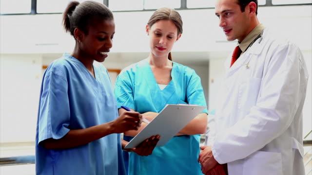 Lächelnd Arzt anhören einer Krankenschwester holding ein Klemmbrett – Video