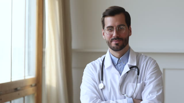 Smiling doctor wear uniform looking at camera standing in office Smiling young man professional medic doctor wear white medical uniform glasses looking at camera standing in hospital office, happy friendly male gp physician surgeon doc close up view portrait general practitioner stock videos & royalty-free footage
