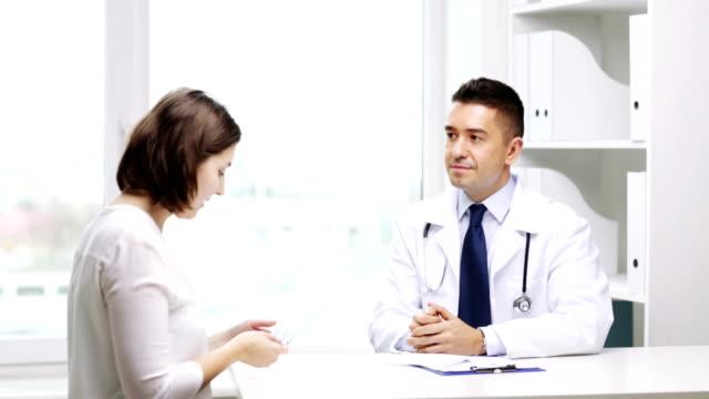 lächelnde arzt mit zwischenablage pillen geben, frau patienten im krankenhaus - familienplanung stock-videos und b-roll-filmmaterial
