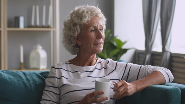 vídeos y material grabado en eventos de stock de sonriente mujer de mediana edad de ensueño sosteniendo una taza de café caliente. - memorial day weekend