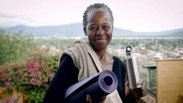 leende äldre afroamerikansksenior kvinna som håller yogamatta och vattenflaska - black woman towel workout bildbanksvideor och videomaterial från bakom kulisserna