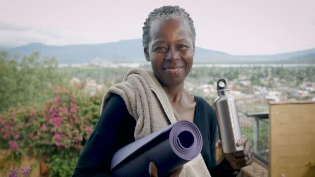leende äldre african american senior kvinna håller yogamatta och vattenflaska - black woman towel workout bildbanksvideor och videomaterial från bakom kulisserna
