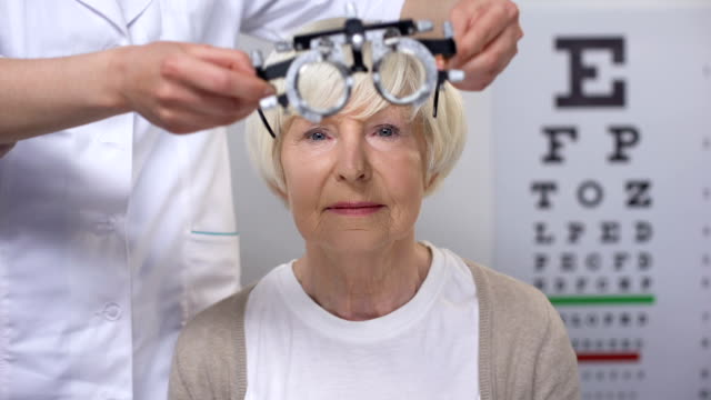 Smiling elderly woman putting on phoropter, choosing proper lens diopter, test Smiling elderly woman putting on phoropter, choosing proper lens diopter, test eye chart stock videos & royalty-free footage