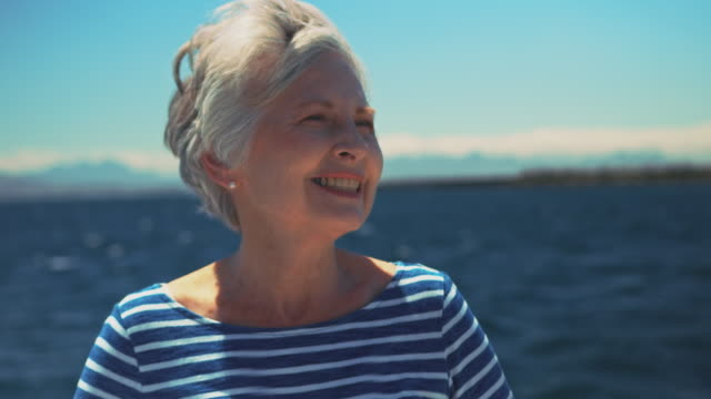 vídeos de stock e filmes b-roll de smiling elderly woman steering yacht in vacation - old lady