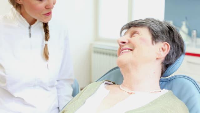 leende äldre kvinna talar med tandläkare - two dentists talking bildbanksvideor och videomaterial från bakom kulisserna