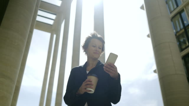 smiling elegant woman with short hair enjoying texting on her mobile phone outdoors with takeaway drink in her hand, low angle tracking shot - krótkie włosy filmów i materiałów b-roll