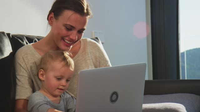 vidéos et rushes de exécutif souriant montrant portable à fils à la maison - femmes actives