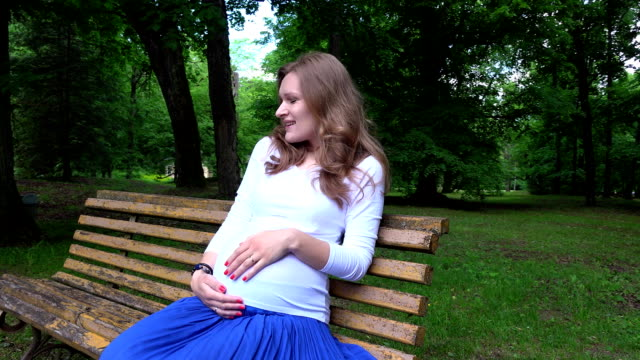 Smiling expectant mother sitting on bench and caress tender her belly in park video