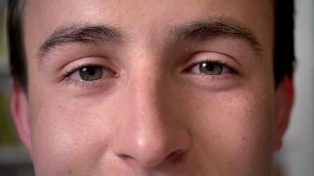 vídeos de stock e filmes b-roll de smiling eyes of young attractive businessman is watching at camera - sobrancelha