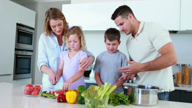 Smiling family preparing a healthy dinner together video