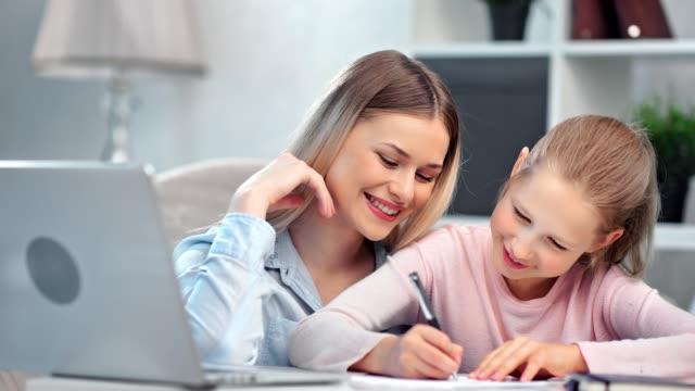 Smiling family studying at home enjoying domestic modern education medium close-up