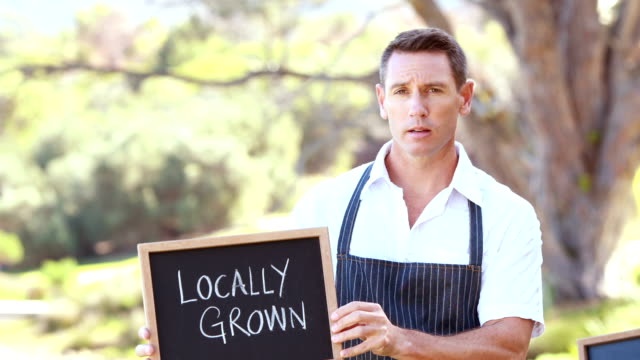 Smiling farmer holding a locally grown sign video