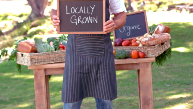 Smiling farmer holding locally grown sign in slow motion video