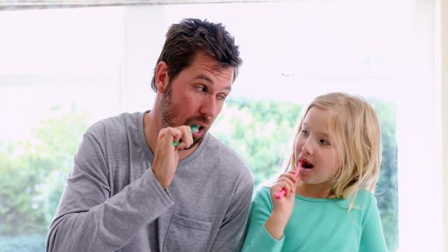 vídeos de stock e filmes b-roll de smiling father and daughter brushing teeth 4k 4k - escovar