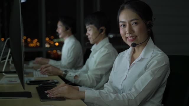 vídeos de stock e filmes b-roll de smiling female customer support phone operator at workplace - envolvimento dos funcionários